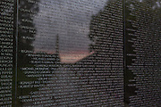 Sunset and the Washington Monument is reflected on the names etched into the Vietnam Veterans Memorial Wall in Washington, DC.
