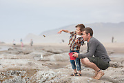 Oliver Whitehead throws rocks into the ocean with his father at Lincoln City beach, Oregon.  Tossing rocks.