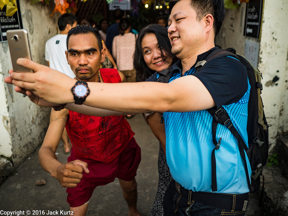 25 SEPTEMBER 2016 - BANGKOK, THAILAND: Thai tourists pose for selfies with a resident of the Pom Mahakan community before a Likay performance in the old fort. Forty-four families still live in the Pom Mahakan Fort community. The city of Bangkok has given them provisional permission to stay, but city officials say the permission could be rescinded and the city go ahead with the evictions. The residents of the historic fort have barricaded most of the gates into the fort and are joined every day by community activists from around Bangkok who support their efforts to stay.      PHOTO BY JACK KURTZ
