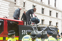 "© Licensed to London News Pictures. 03/10/2019. London, UK. Extinction Rebellion protesters are arrested by police after using a fire engine to spray the front of the Treasury building with fake blood. Extinction Rebellion said it wanted to highlight the ""inconsistency between the UK Government's insistence that the UK is a world leader in tackling climate breakdown, while pouring vast sums of money into fossil exploration and carbon-intensive projects"". Photo credit: Ray Tang/LNP"