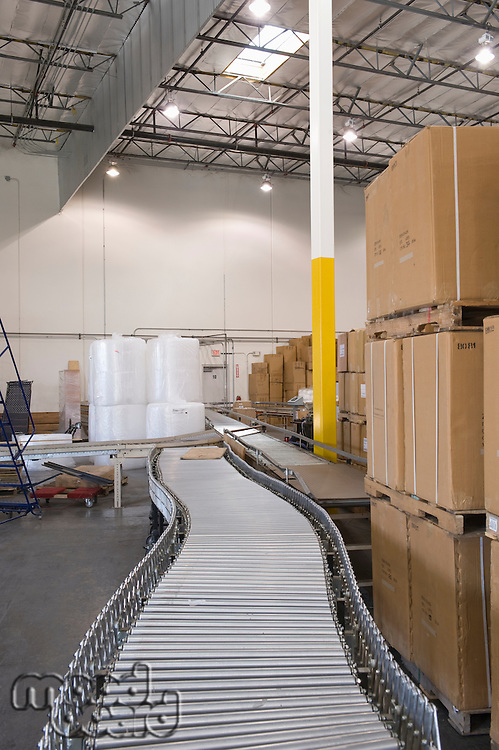 Cardboard boxes and conveyor belt in distribution warehouse