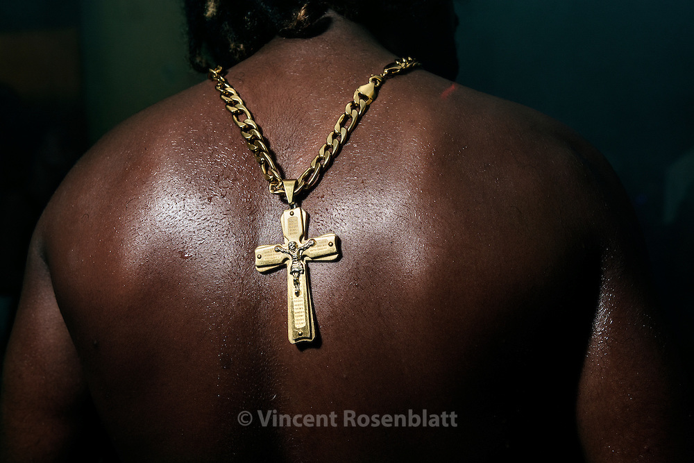 "Crucifix on MC Tchelinho's back, performing at ""Heavy Baile"" party at the Cruzada São Sebastião favela,  Leblon, Rio de Janeiro..The Funk carioca movement is fashion and look as well : The boys show off their muscles and naked torsos, adorned with chains and tattoos, accessories which will make the difference during the ball. Girls will look after their bikini marks, which will appear above mini-skirts or micro-shorts. Everything is worth to draw attention!"