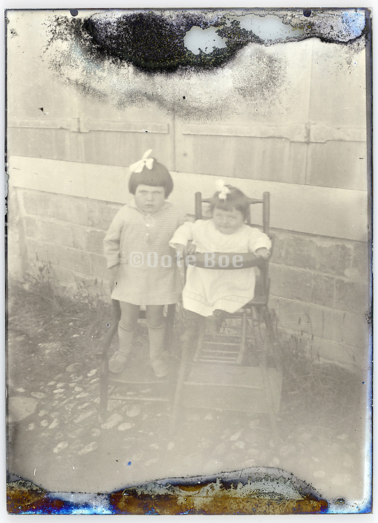 little sister with toddler baby in high lunch chair posing early 1900s