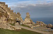 Remains of the battlemented curtain wall, built 1240-60, which surrounded the island courtyard of Tintagel Castle, built by Richard, 1st Earl of Cornwall in the 13th century, Tintagel Island, Cornwall, England. The ruined castle is linked with Arthurian Legend, as Geoffrey of Monmouth cited it as the place of conception of King Arthur in his 12th century book, History of the Kings of England. The site is managed by English Heritage. Picture by Manuel Cohen