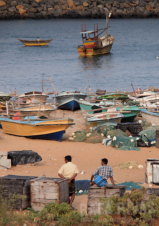 Men stand next o fishing boats at the Hanbantota sea-port, in Sri Lanka, on February 26, 2011
