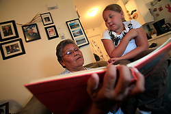 CANADA ALBERTA FORT CHIPEWYAN 22JUL09 - Cancer patient Emma Michael shows her granddaughter Donya Wandering Spirit a family photo album at her home in Fort Chipewyan, northern Alberta, Canada...Mrs Michael survived an aggressive breast cancer tumor and believes that her cancer was caused by increased levels of pollution to the air and water downstream from the tarsands sites. Five of her relatives, displayed on the wall behind her, have died of various forms of cancer in recent years...jre/Photo by Jiri Rezac / GREENPEACE..© Jiri Rezac 2009