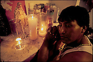 IMMOKALEE, FLORIDA: A migrant farm laborer from Guatemala prays at a small shrine to the Virgin Mary he set-up in his home. He said the Virgin brings him peace and safety.  (Photo by Robert Falcetti). .