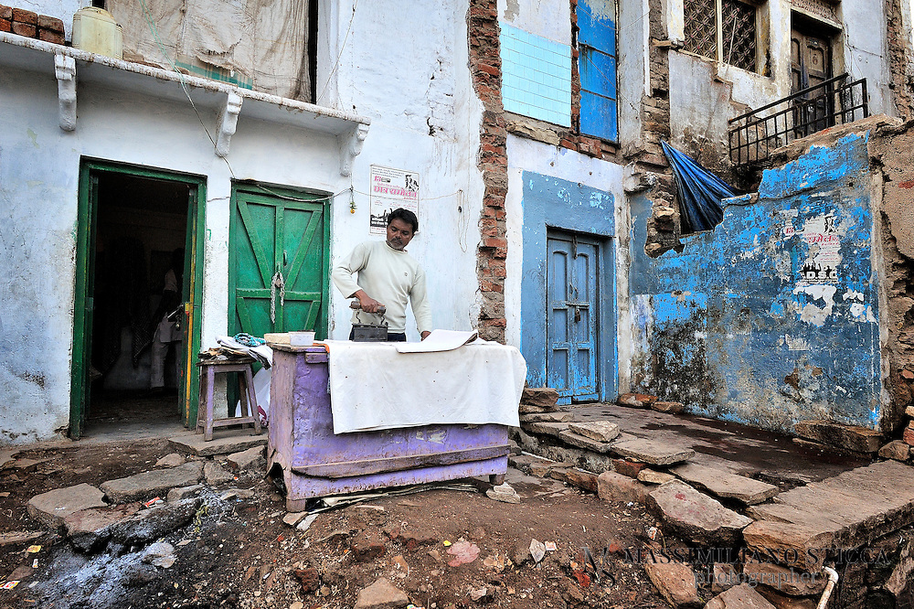 A street in Gwalior, a man ironing outside his home.