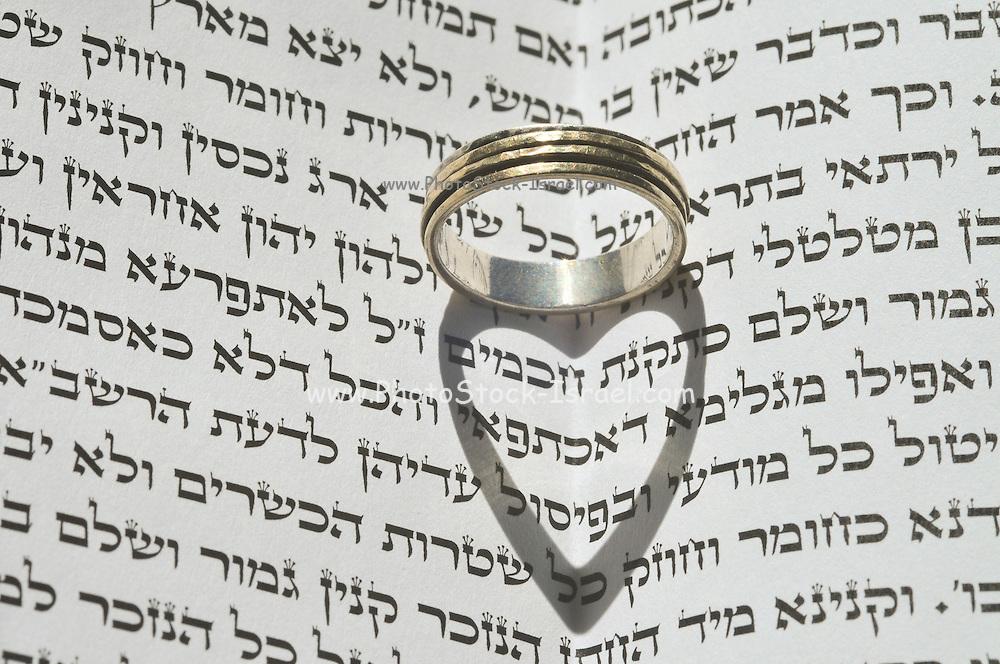 Jewish Wedding concept Wedding ring on Jewish Text (Ketubah)