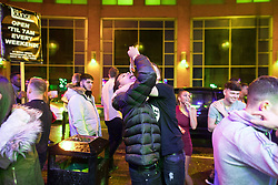 """© Licensed to London News Pictures . 23/12/2017. Manchester, UK. A man eats kebab meat outside a takeaway on Withy Grove . Revellers outside the Printworks in Manchester City Centre overnight during """" Mad Friday """" , named for being one of the busiest nights of the year for the emergency services in the UK . Photo credit: Joel Goodman/LNP"""