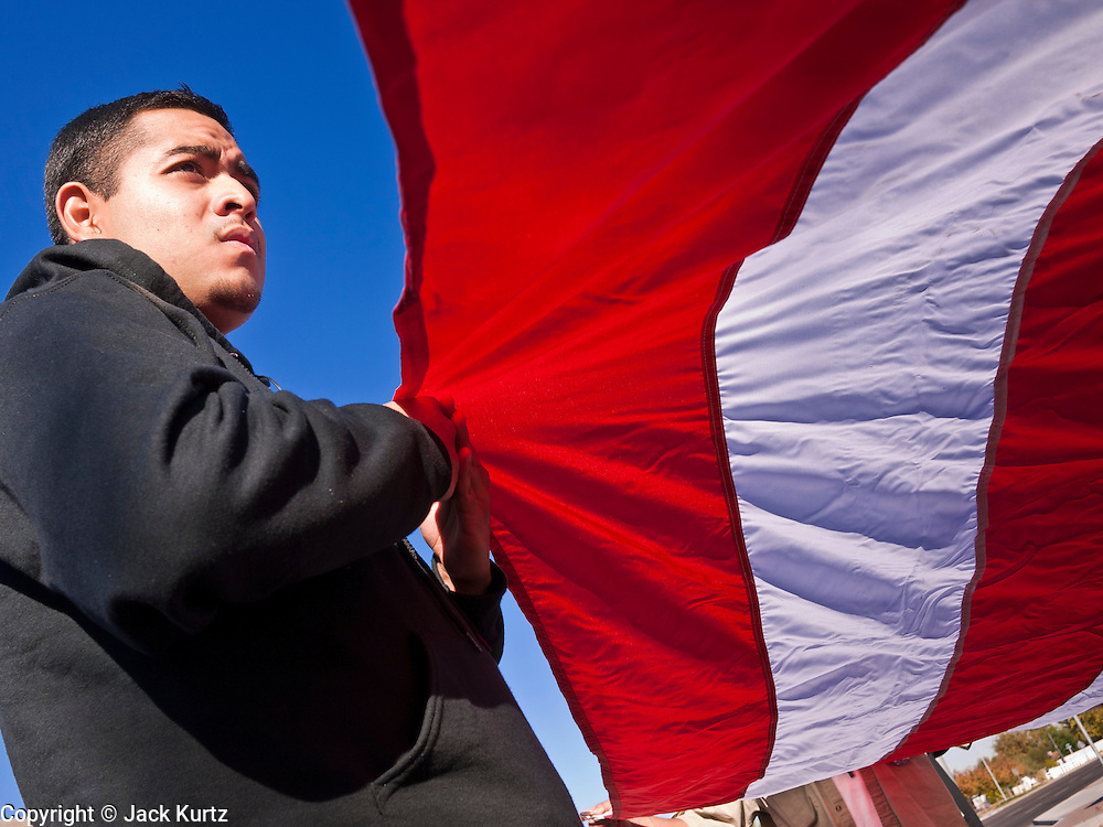 "07 DECEMBER 2010 - PHOENIX, AZ:  Supporters of the DREAM Act hold up a large American flag in front of the offices of US Sen. John McCain in Phoenix Tuesday. Dolores Huerta, who started working in the civil rights movement in the 1960's, threw her support behind students fasting on behalf of the DREAM Act in front of Sen. John McCain's office Tuesday. The student picked McCain's office because he used to support the DREAM Act. They hope that the US Senate will pass the DREAM Act during its ""lame duck"" session. The Senate debated and defeated similar legislation just before the November general election.   PHOTO BY JACK KURTZ"