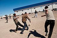 Des réfugiés jouent au foot pour passer le temps au poste frontière de Ras Jedir. Plus de 140 000 réfugiés ont déjà quitté la Libye par la Tunisie ou l'Egypte et des milliers continuent d'arriver chaque jours. Mercredi 2 Mars 2011, poste frontière de Ras Jedir, Tunisie..© Benjamin Girette / AP