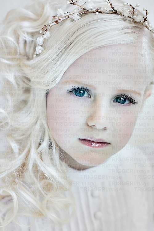 Young girl with pearls in blonde curly hair wearing white dress looking at camera