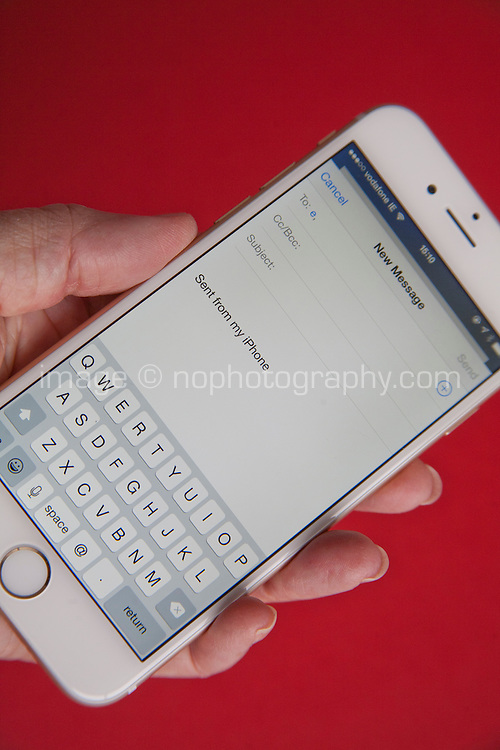 Sending an email on a Gold and white Apple iPhone 6 against a red background