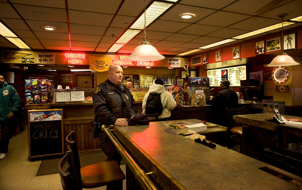 Pittsburgh Police Officer James Snyder visits with the crew at Sammy's Famous Corned Beef in Liberty Avenue.