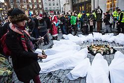 London, UK. 21st December, 2018. Environmental campaigners from Extinction Rebellion scatter ashes to remember the 27 people found burnt alive in the Greek village of Mati after July's wildfires during a protest outside Broadcasting House against the lack of coverage by the BBC of the climate change crisis.