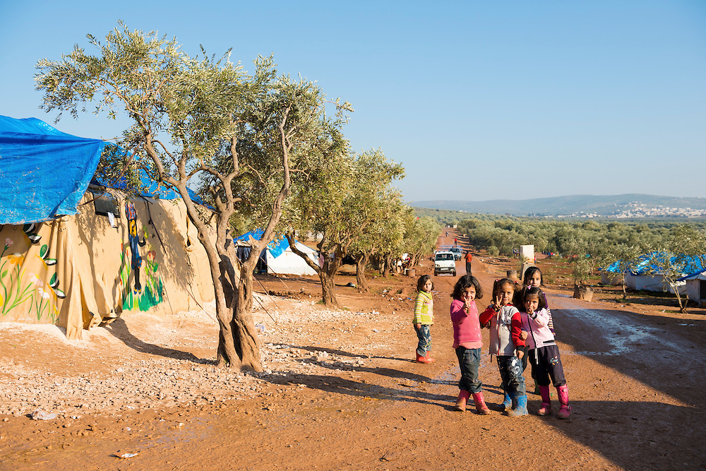 Several girls stand outside a school (left) set up at a camp for displaced persons in Atmeh, in northern Syria. Around 11,000 people were living in the camp in early 2013, driven from their homes elsewhere in Syria by violence.