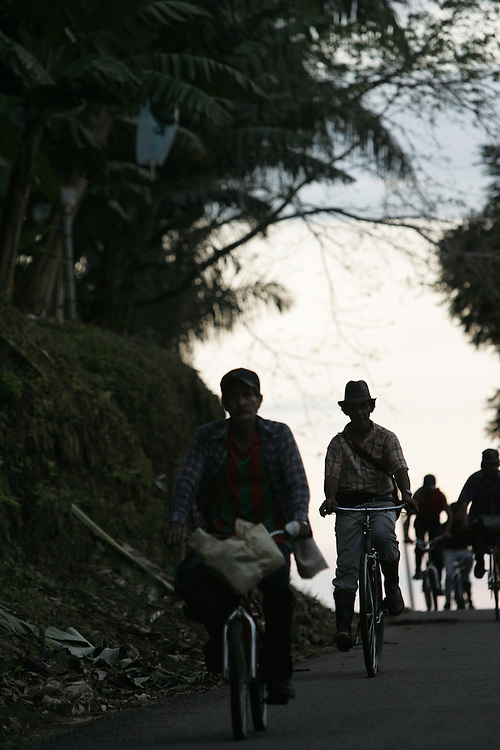 Men ride bikes outside of a small town in the heart of Colombian coffee country. The tourism industry is slowly emerging in Quindio, the Colombian coffee country.  Old coffee haciendas have been turned into new hotels catering to tourists.  The countryside, some of the most beautiful in the country, is a popular weekend getaway spot where visitors can participate in a variety of outdoor activities as well as learn about coffee production.