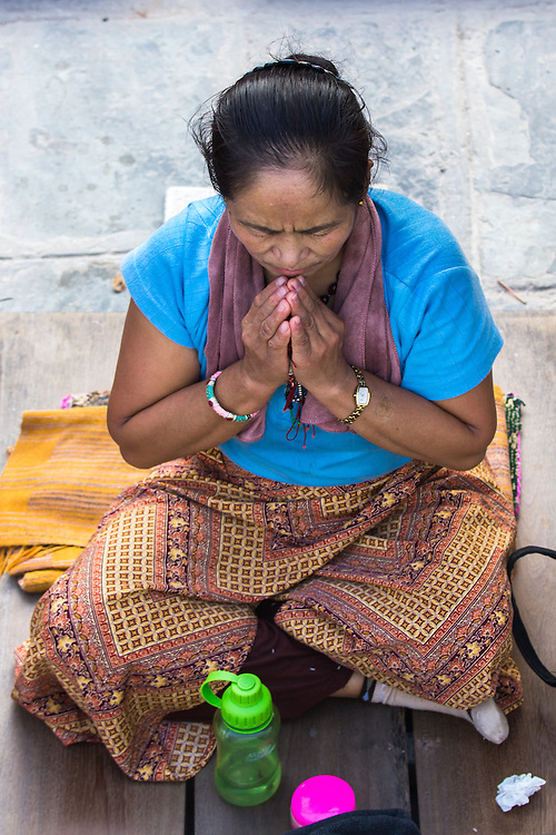 Buddhist woman praying at the Bodnath stupa early in the morning. Kathmandu, Nepal.<br />