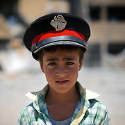 August 11, 2012 - Tarafat, Aleppo, Syria: A syrian child, wearing a policeman hat, poses in front of the Jamal-Jamal school in Tarafat village, near Aleppo. The Syrian Army warplanes have recently bombed residential areas and the only two schools in the village, with 200 kilogram bombs. (Paulo Nunes dos Santos/Polaris)