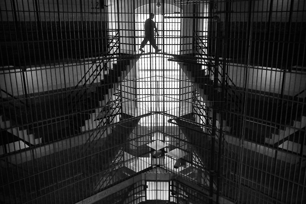 An inmate walks back to his cell after being out in the courtyard.  The Bristol County Jail & House of Correction located on Ash Street in New Bedford, Massachusetts was started in 1829, and is the oldest running jail in the United States.   The Ash street jail, as it is known, has been a controversial facility since it opened.  It is believed to be the site of the last pubic hanging in Massachusetts sometime in the 1890's.  Two big riots broke out in the 90's (1993, 1998) and since then the facility has been modified to alleviate some of the crowded conditions that resulted in the riots.