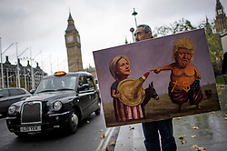 © Licensed to London News Pictures. 09/11/2016. London, UK. Artist KAYA MAR holds up a painting depicting US presidency candidates, Hilary Clinton and Donald Trump, outside the Houses of Parliament in London. Donald Trump will become the 45th president of the United States following a shock election victory late last night in the USA.  Photo credit: Ben Cawthra/LNP