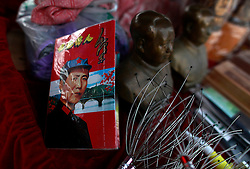 A booklet showing former Chinese Communist leader Mao Zedong in a Red Army uniform along with other memorabilia on a souvenir stall at the Longtan waterfall tourist site in Jinggangshan of Jiangxi Province, China, 15 October 2012. Jinggangshan or Jinggang mountain is a popular destination for Red Tourism where Chinese communist party cadres and ordinary Chinese tourists alike converge, seeking to relive the experiences and rekindle the spirit of the revolutionaries. It is deemed as the birthplace of the Chinese Red Army and the 'cradle of the Chinese revolution' which saw Communist leader Mao Zedong's ascent to power as a revolutionary. After a failed uprising in 1927, Mao fled into the mountains with his 1,000 remaining troops from nationalist forces and set up base here to reorganize his army, eventually defeating the Kuomingtang (KMT) to rule the country. Cadres dressed in Red Army uniforms attending Communist party training courses in are a common sight in the various historical sites of the mountain where they sing red songs and retrace the paths taken by their forbears. The Chinese communist party is slated to hold its 18th national congress on 08 November where a major leadership transition will see current leaders President Hu Jintao and Premier Wen Jiabao make way for a new generation of leaders helmed by Xi Jinping, With more than 80 million members, the Chinese Communist Party is hard pressed to display a show of unity and power after  scandals the ousting of disgraced politician Bo Xilai roiled the country. .