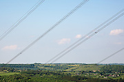 Overhead power lines diagonally cross the Cotswold landscape of rolling hills and fields Ravensgate Hill in Gloucestershire, England.