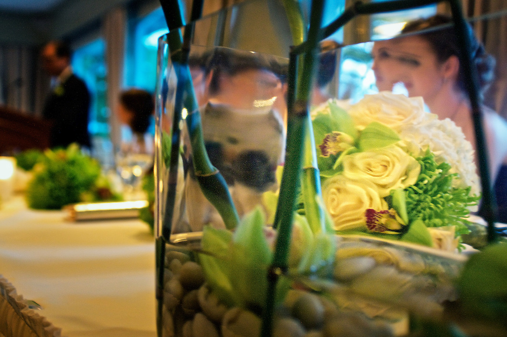Flowers viewed through potted glass vase during indoor reception.