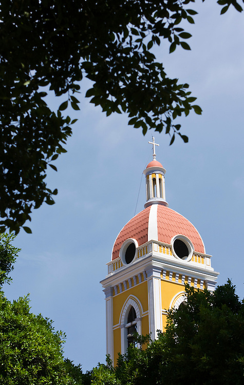 The spire of Granada Cathedral seen through the trees that cover the town square. Granada is Nicaragua's most famous city. founded in 1524 it is one of best examples of Spanish colonial architecture in the Americas. .it has a varied history including its almost total destruction by filibuster William Walker in a childlike tantrum. Today it is a popular tourist town though retains a strong sense of its own identity.