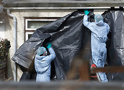 © Licensed to London News Pictures. 14/03/2018. London, UK. Police wearing protective clothing cover the rear windows of the house of Russian exile Nikolai Glushkov as they continue their investigation in south west London. Mr Glushkov, a friend of oligarch Boris Berezovsky, and a former deputy director of Russian state airline Aeroflot, died at his home in Monday night. Photo credit: Peter Macdiarmid/LNP