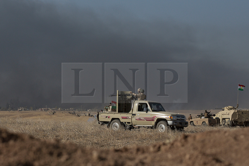 20/10/2016. Bashiqa, Iraq. With the smoke from coalition airstrikes in the background, peshmerga fighters are seen near the Iraqi town of Tiskharab near Mosul city, during an offensive to retake the Bashiqa area today (20/10/2016).<br /> <br /> Launched in the early hours of today with support from coalition special forces and air strikes, the attack is part of the larger operation to retake Mosul from the Islamic State, and involves both the Kurds and the Iraqi Army. The city of Bashiqa, around 9 miles north of Mosul, is one of several gateway areas that must be taken before any attempted offensive on Mosul itself.<br /> <br /> Despite the peshmerga suffering several casualties after militants fought back using mortars, heavy machine guns and snipers, the Kurdish forces were quickly taking ground with Haider al-Abadi, the Iraqi prime minister, stating that the operation to retake Mosul was progressing faster than expected. Photo credit: Matt Cetti-Roberts/LNP