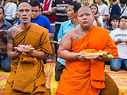 "07 MARCH 2015 - NAKHON CHAI SI, NAKHON PATHOM, THAILAND:  Buddhist monks pray at the Wat Bang Phra tattoo festival. Wat Bang Phra is the best known ""Sak Yant"" tattoo temple in Thailand. It's located in Nakhon Pathom province, about 40 miles from Bangkok. The tattoos are given with hollow stainless steel needles and are thought to possess magical powers of protection. The tattoos, which are given by Buddhist monks, are popular with soldiers, policeman and gangsters, people who generally live in harm's way. The tattoo must be activated to remain powerful and the annual Wai Khru Ceremony (tattoo festival) at the temple draws thousands of devotees who come to the temple to activate or renew the tattoos. People go into trance like states and then assume the personality of their tattoo, so people with tiger tattoos assume the personality of a tiger, people with monkey tattoos take on the personality of a monkey and so on. In recent years the tattoo festival has become popular with tourists who make the trip to Nakorn Pathom province to see a side of ""exotic"" Thailand.  PHOTO BY JACK KURTZ"