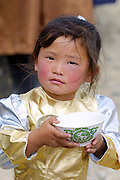 GOBI DESERT, MONGOLIA..08/26/2001.Bayangovi. Girl at local Naadam festival with bowl of mares' milk..(Photo by Heimo Aga).