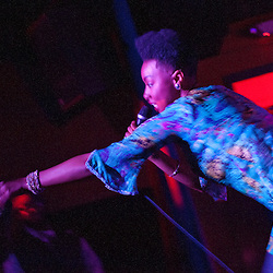 """Washington, DC  - Carolyn Malachi grabs a cell phone from the audience and weaves a rhyme about it at Tropicalia for the """"Sleepless in Soweto"""" album release party."""