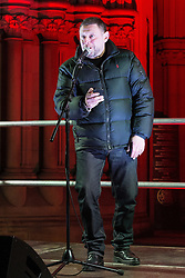 """© Licensed to London News Pictures . 03/02/2015 . Manchester , UK . Madchester star SHAUN RYDER reads a short speech from his phone to the crowd , at the demonstration . Demonstration organised by the Labour Party on the steps of Manchester City Council in Albert Sqaure , Manchester , under the banner """"manVcam"""" ( Manchester vs Cameron ) . Organisers say Manchester - along with Liverpool and Birmingham - have suffered larger cuts than other regional authorities , whilst southern regions such as Surrey , Hampshire and West Sussex have all seen increases in government funding . Photo credit : Joel Goodman/LNP"""