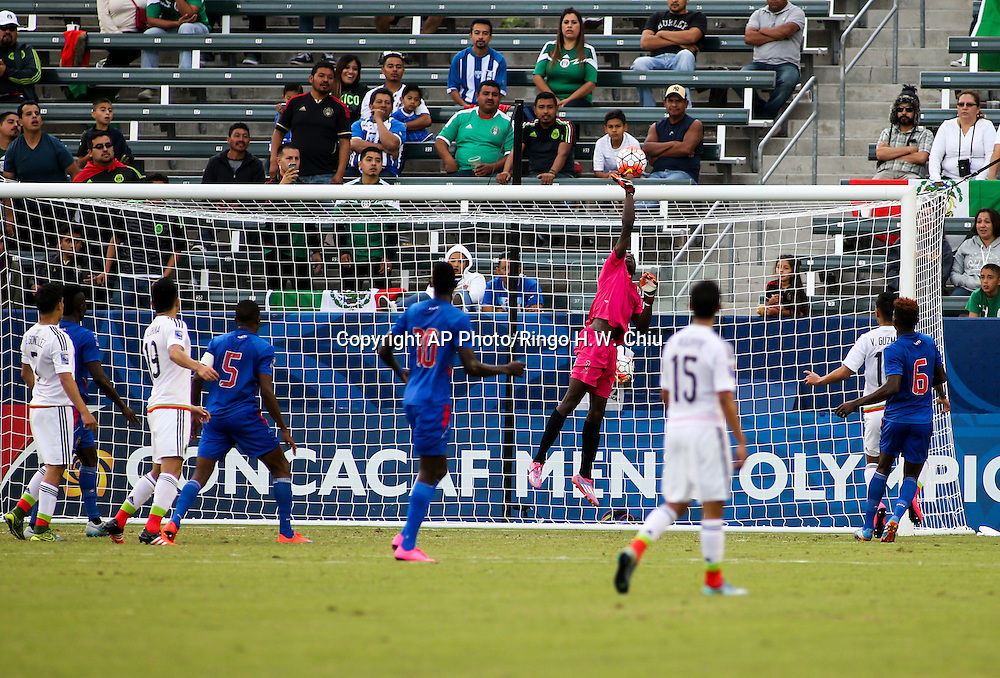 Haiti goalkeeper Luis Valendi Odelus #1 makes a save against Mexico in the first half of a CONCACAF men's Olympic qualifying soccer match in Carson, Calif., Sunday, Oct. 4, 2015. (AP Photo/Ringo H.W. Chiu)
