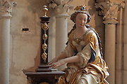 Painted statue of St Cecilia playing a portable organ, by Charles Hoyau, commissioned 1633 by canon Bernardin Le Rouge, for an altar to be placed under the grand organ in honour of a musical competition, and moved here in 1974, in the Chapelle Saint Pierre or St Peter's Chapel in the Cathedrale Saint-Julien du Mans or Cathedral of St Julian of Le Mans, Le Mans, Sarthe, Loire, France. The statue was repainted in the 19th century and restored 1997-2002 by Brigitte Esteve and Pierre Gicquel. The cathedral was built from the 6th to the 14th centuries, with both Romanesque and High Gothic elements. It is dedicated to St Julian of Le Mans, the city's first bishop, who established Christianity in the area in the 4th century AD. Picture by Manuel Cohen