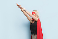 Young woman in superhero outfit pretending to leap in the air against light blue background