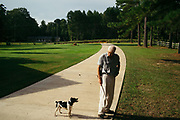 "MERIDIAN, MS – AUGUST 3, 2018: Clayton George, 57, surveys the family property alongisde his dog, Poupon. As a resident of Tennessee, George makes the four hour drive south every two weeks to check on his family's 400 acre tract and visit his father who still lives there.<br /> <br /> In 1987, George and a friend walked in rows planting the family's first batch of Loblolly pine, where soybeans, wheat and cattle once covered the family's 400 acres.  The shift to timber was largely prompted by the Conservation Reserve Program, a popular new farm subsidy in the 1980s that encouraged farmers to reforest depleted land by paying them for every acre of trees planted. Since 1926, the George family had made a good living from their eastern Mississippi farm, but the decline of soybeans and other crops eventually led George to consider growing trees instead – a crop that landowners throughout the south believed would bring in easy money. Thirty years later, however, the same landowners are now facing unexpected financial hardship. Stumpage prices have been on a steady decline – as much as 45% since 2007 – and landowners are rethinking timber as a worthwhile investment. """"We figured we''d plant trees and come back and harvest it in 30 years, and in the meantime go into town to make a living doing something else,"" George said. As co-owner of the family acreage with three other family members, George always considered himself the most nostalgic Now, as he patiently awaits for right time to harvest a 30 year investment, even he considers the future of the land uncertain. CREDIT: Bob Miller for The Wall Street Journal<br /> TIMBER_AL"
