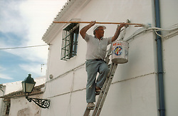 Man painting the outside of a house in Antequera; Andalucia,
