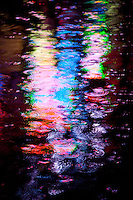 Amsterdam, Holland. Rain splash reflection of neon lights in  a canal in the red light district.