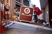 Equipment managers work in the Mal Moore Athletic Facility to get the University of Alabama football team ready for the trip to Baton Rouge to face LSU.  John Bartlett and Leon Fluker have a little fun loading a crate on the truck.  The two student managers, the shortest and tallest of the crew, can often be seen walking side by side as they take care of business.  Leon Fluker's brother DJ Fluker plays on the offensive line for Alabama.  Photo by Gary Cosby Jr.