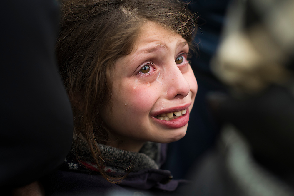 Sidra, a 10 year-old Syrian refugee, cries as tensions rise near a gate in the fence at a refugee camp on the Macedonian (FYROM) border on March 6, 2016 in Idomeni, Greece.