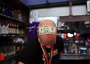 A bartender with a five dollar bill stuck to his head on the Las vegas Strip.