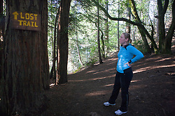 """A woman hiking on a trail stops to read a sign that says """"Lost Trail"""" at a split in the path, Muir Woods National Monument, Marin County, California, United States of America"""