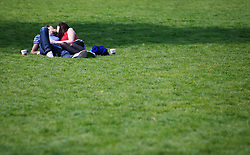 © Licensed to London News Pictures 24/04/2013.A couple embrace whilst enjoying the warm weather and sunshine in St James Park, central London..London, UK.Photo credit: Anna Branthwaite/LNP