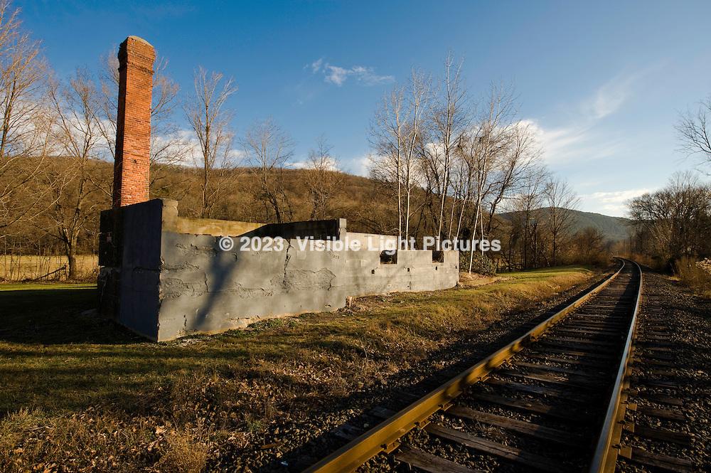 Foundation and chimney along railroad tracks.