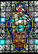 Stained glass image of lamb of God carrying vexillum and depicting Christ's triumph over death. (Sam Lucero photo)