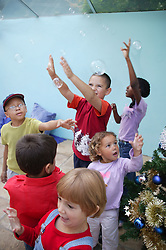 Group of children reaching in the air for bubbles,
